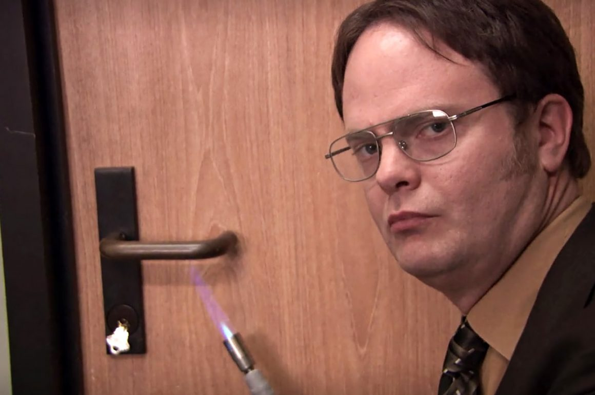 Dwight from The Office heating up a door handle with a torch