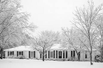 suburban ranch home with snow