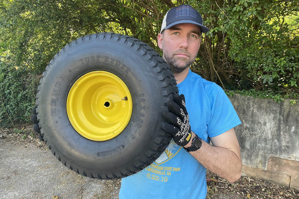 Dave Greenwood holding a John Deere lawn tractor rear tire and wheel